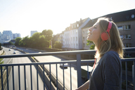 Smiling young woman on a bridge listening music with headphones - KNSF03148