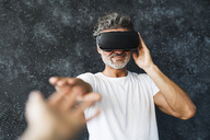 Mature man wearing VR glasses reaching out with hands - HAPF02467
