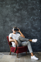 Mature man looking through VR glasses, sitting in armchair - HAPF02470