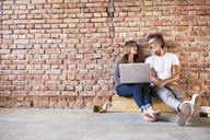 Businessman and woman sitting in a loft, using laptop, founding a start-up company - HAPF02479