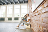 Businessman and woman sitting in a loft, using laptop, founding a start-up company - HAPF02482
