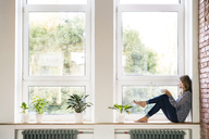 Woman sitting at home on the window sill, drinking coffee - HAPF02488