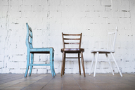 Empty chairs against white brick wall - HAPF02503