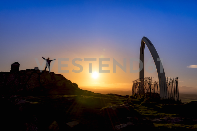 Great Britain, Scotland, East Lothian, North Berwick, North Berwick Law, whale jaw bone arch, sunset, female tourist with raised arms - SMAF00901