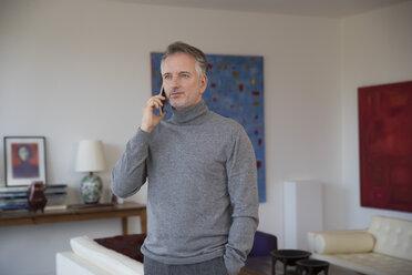 Businessman using smartphone in apartment - SUF00376