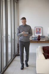Businessman using tablet in apartment - SUF00379