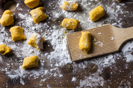 Preparing pumpkin gnocchi, rolling on wooden board - SBDF03395