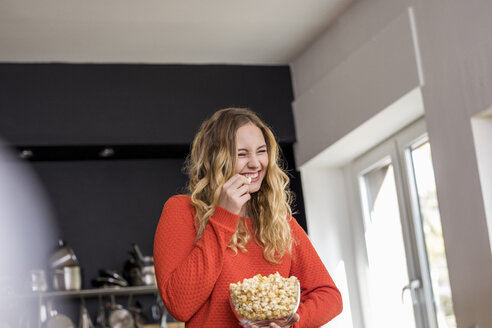 Portrait of giggling young woman with bowl of popcorn in the kitchen - FMKF04653