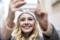 Portrait of laughing young woman taking selfie with smartphone - FMKF04662
