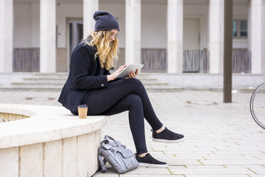 Young woman with coffee to go sitting on a wall using tablet - FMKF04668