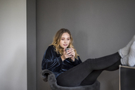 Portrait of young woman with hot beverage at home - FMKF04671
