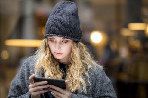 Portrait of serious young woman using smartphone - FMKF04674