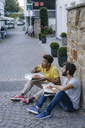 Two friends eating takeaway pizza in the city - KNSF03169