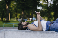 Man with cell phone lying in skatepark - KNSF03175