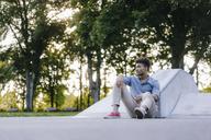 Portrait of relaxed man sitting in skatepark - KNSF03187