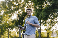 Smiling young man holding cell phone in park - KNSF03190