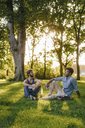 Two friends sitting in a park with mobile device and papers - KNSF03199