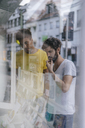 Two friends in the city looking in shop window of a bookstore - KNSF03202