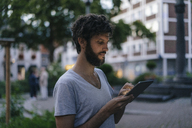 Man looking at phablet in the city at dusk - KNSF03205