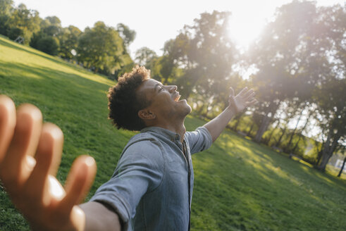 Young man enjoying the sunset in a park - KNSF03217