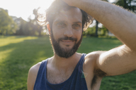 Portrait of smiling man with beard at sunset in a park - KNSF03220
