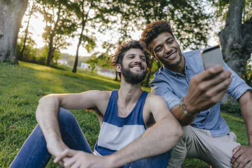 Two happy friends sharing cell phone in a park - KNSF03235