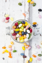 Glass of colourful sweet jellybeans on white wood - LVF06490