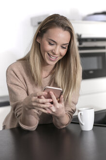 Portrait of smiling blond woman using cell phone at home - GDF01174