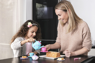 Mother and little daughter little  playing together with doll's china set - GDF01177