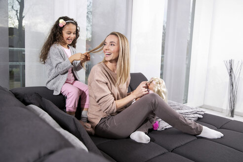Little girl braiding her mother's hair on the couch - GDF01180