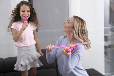 Mother and little daughter playing together with toy violin - GDF01183