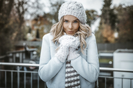 Portrait of smiling woman wearing woolly hat, gloves and scarf - GDF01186