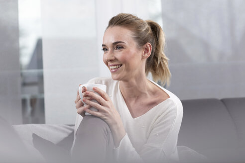 Portrait of happy woman with coffee mug at home - GDF01195