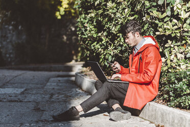 Italy, Verona, tourist using smartphone and laptop - GIOF03575