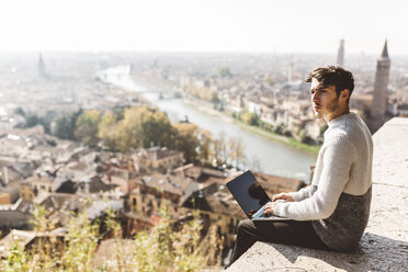 Italy, Verona, tourist using laptop, observation point - GIOF03581