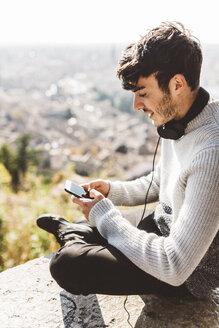 Italy, Verona, tourist using smartphone, headphones - GIOF03584