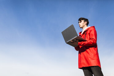 Blue sky, young man using laptop - GIOF03587