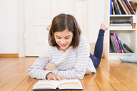 Smiling girl lying on the floor reading book - LVF06497