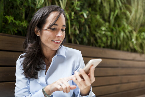 Smiling businesswoman using cell phone in garden cafe - VABF01396