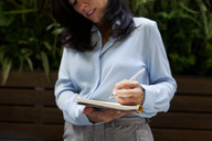 Close-up of businesswoman taking notes - VABF01399