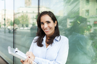 Portrait of smiling businesswoman holding notebook in the city - VABF01408