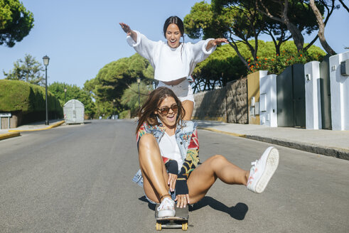 Two laughing friends together on skateboard - KIJF01743