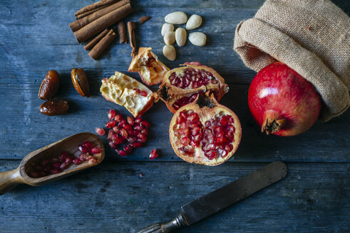 Sliced and whole pomegranate, pomegranate seed, dates, almonds and cinnamon sticks on wood - KIJF01773