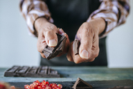 Man's hands breaking a chocolate bar, close-up - KIJF01776