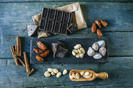 Dates, dark chocolate, almonds, cinnamon sticks  and dried figs on wood - KIJF01782
