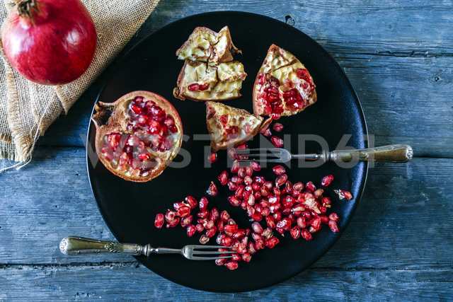 Half of pomegranate, pomegranate seed and two old forks on black plate - KIJF01785