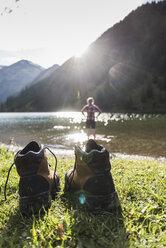 Austria, Tyrol, hiking shoes and woman refreshing in mountain lake - UUF12477