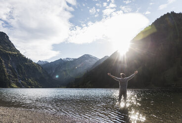 Austria, Tyrol, hiker standing with outstretched arms in mountain lake - UUF12480