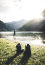 Austria, Tyrol, hiking shoes and man standing with outstretched arms in mountain lake - UUF12483