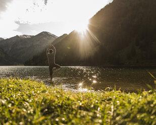 Austria, Tyrol, hiker in yoga pose refreshing in mountain lake - UUF12486